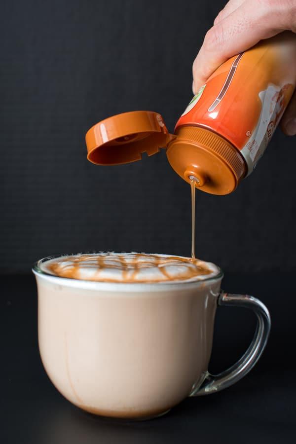 Drizzling the Caramel Macchiato with Caramel Sauce.