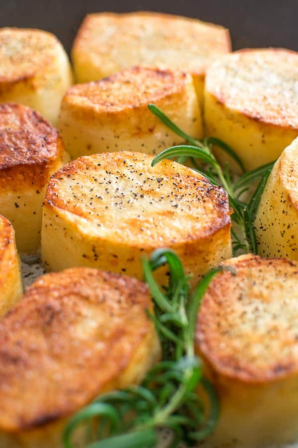 Fondant Potatoes with rosemary in the skillet