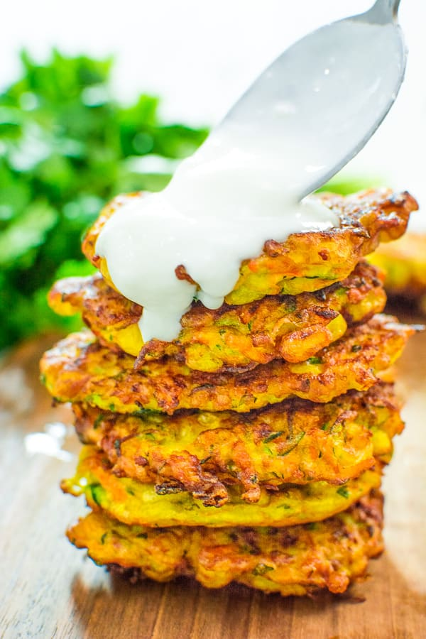 Pouring yogurt over vegetable fritters
