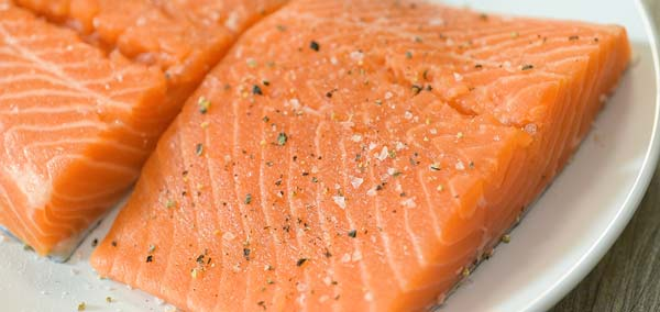 seasoning the salmon with salt and pepper