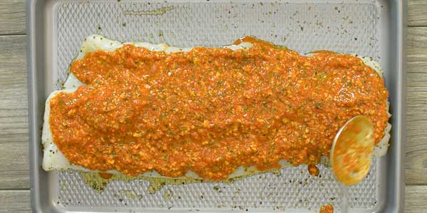 spreading roasted pepper paste on the cod fish