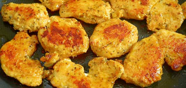 frying marinated chicken on a skillet