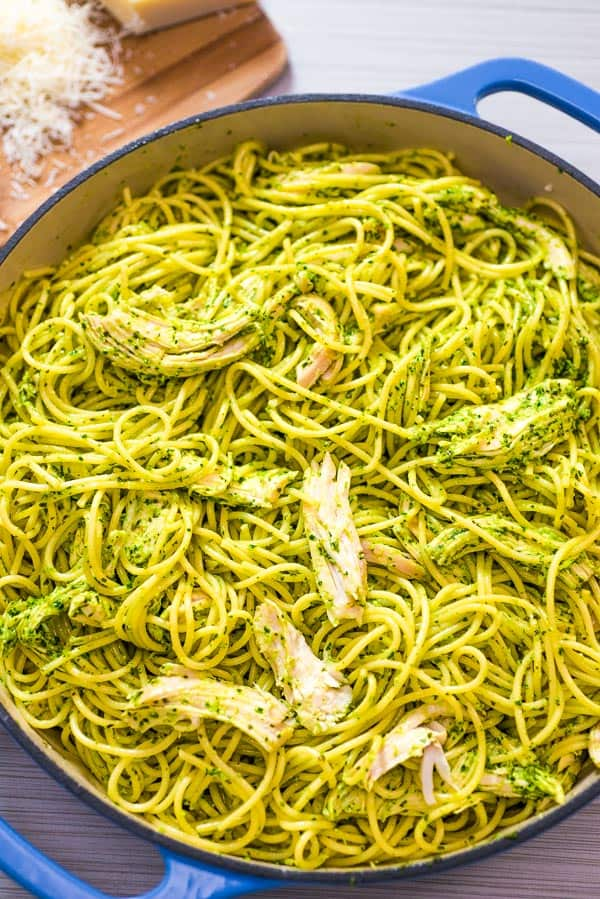 Chicken Pesto Pasta in a skillet with Parmesan Cheese on the background