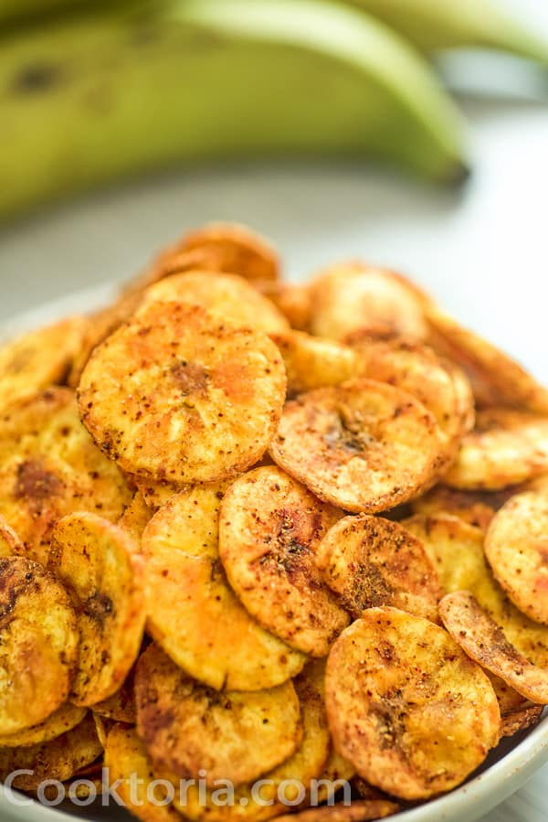 Baked Plantain Chips in a bowl, and plantain fruits on the background