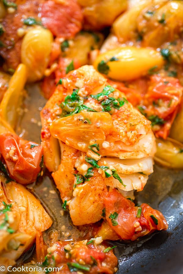 Cod Fish in the skillet covered with tomato sauce
