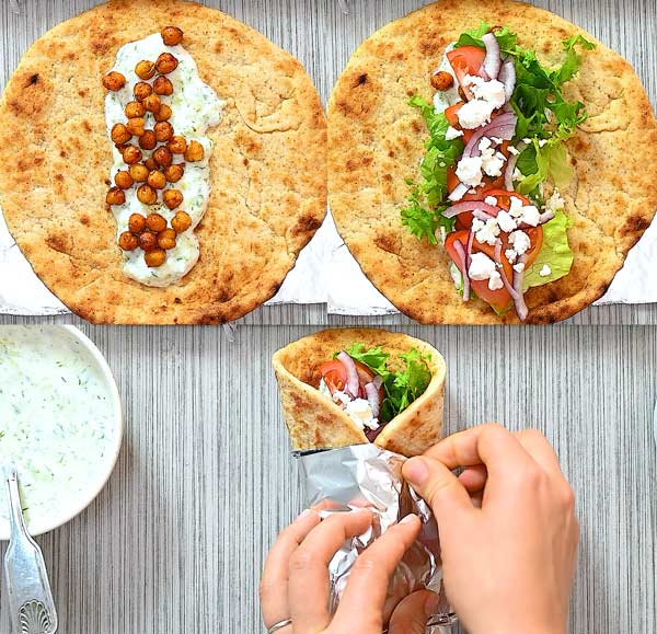 adding ingredients to the gyro and folding it