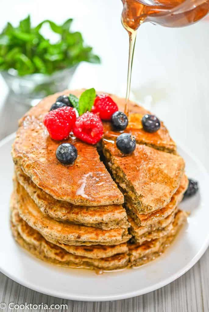 Pouring Maple Syrup over Healthier Pancakes