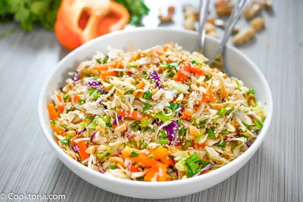 Asian slaw in a bowl with vegetables on the background