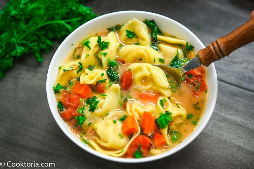 tortellini soup in a white bowl