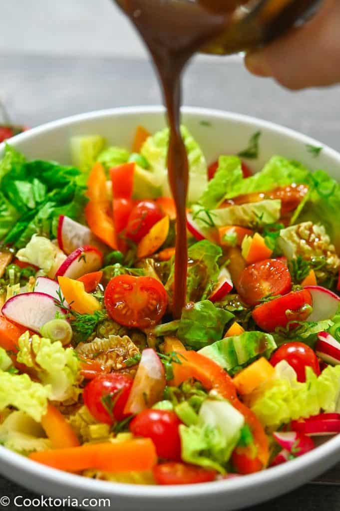 pouring the dressing onto a salad
